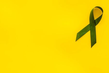 Green ribbon as symbol of disease control on yellow background top view copy space 写真素材