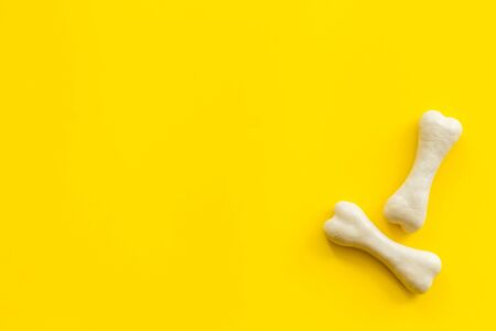 Treats for dogs. Chewing bones on yellow background top view copy space Фото со стока - 133281269