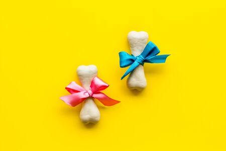 Small present for dogs. Chewing bones with bow on yellow background top view. Фото со стока