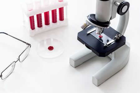 Blood testing laboratory. Samples viewing under microscope near tubes on white background top view copy space