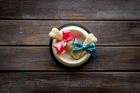 Dogs birthday concept. Chewing bones with bow in bowl on dark wooden background top view copy space