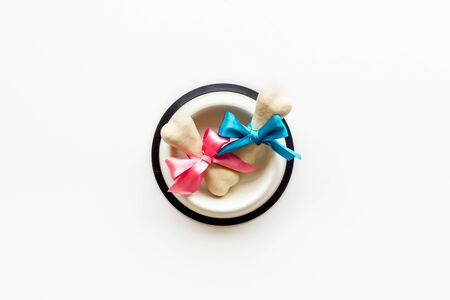 Dogs birthday concept. Chewing bones with bow in bowl on white background top view space for text