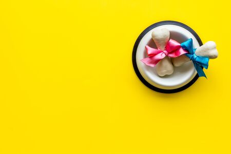 Dogs birthday concept. Chewing bones with bow in bowl on yellow background top view copy space Фото со стока - 133352471