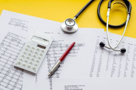 Health insurance concept. Stethoscope near financial documents and calculator on yellow background. Stock fotó - 133415181