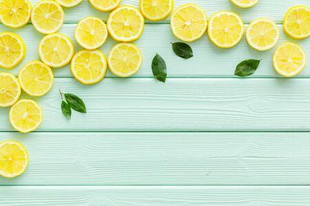 Lemon frame. Sliced citruses on green wooden background top view.