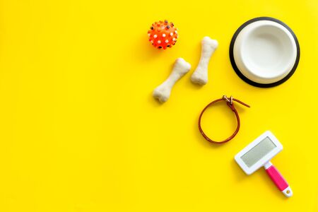 Set of treats and toys for pets with bones, collar and bowl on yellow background top view frame copy space Фото со стока - 133352468