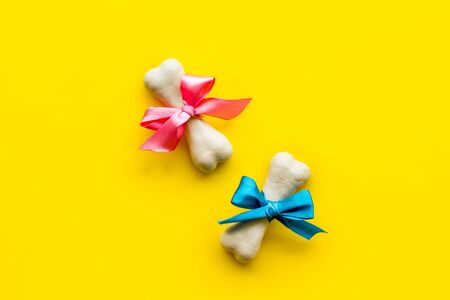 Small present for dogs. Chewing bones with bow on yellow background top view copy space