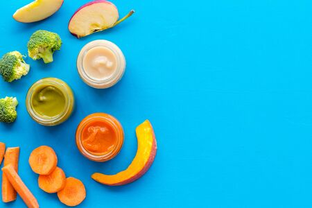 Vegetable and fruits puree for feed babies on blue background top view.