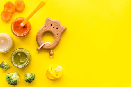 Vegetable and fruits puree for feed babies on yellow background top view.