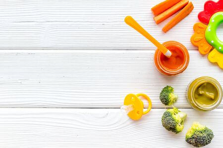 Vegetable and fruits puree for feed babies on white wooden background top view.