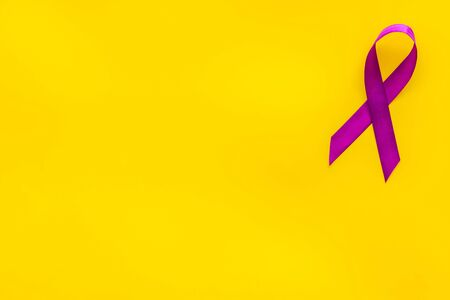 Lavender ribbon is symbol of Alzheimers disease on yellow background top view.