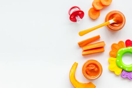 Orange baby food. Puree near pumpkin and carrot on white background top view. Stock Photo