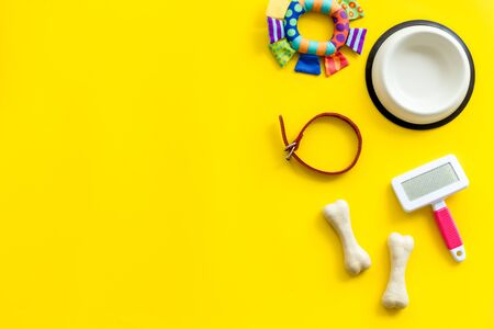 Set of treats and toys for pets with bones, collar and bowl on yellow background top view. Фото со стока - 133417058