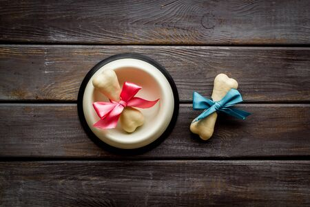 Dogs birthday concept. Chewing bones with bow in bowl on dark wooden background top view. Фото со стока