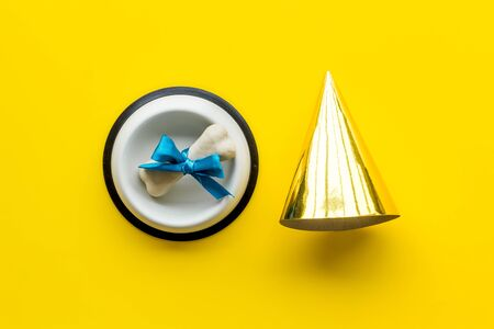 Dogs birthday concept. Chewing bones with bow and party hat on yellow background top view.