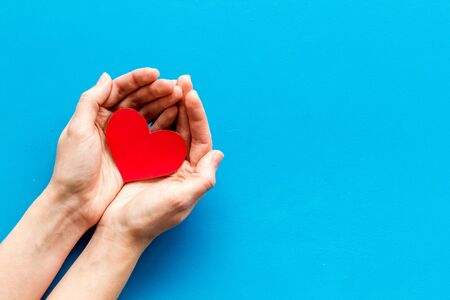 Heart icon. Paper heart in hands on blue background top view. Imagens