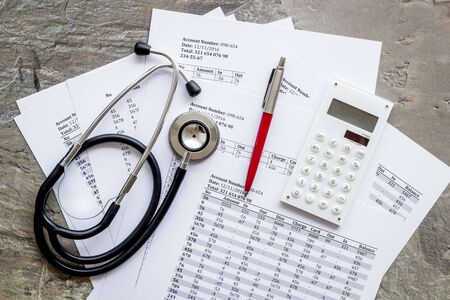 Health insurance concept. Stethoscope near financial documents and calculator on grey background top view. Stock fotó