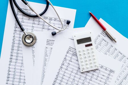 Health insurance concept. Stethoscope near financial documents and calculator on blue background top view.
