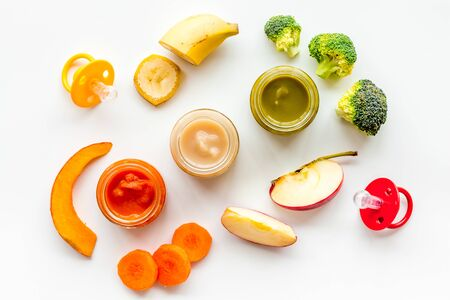 Baby food. Colorful puree in glass jars near vegetables and fruits on white background top view.