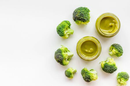 Mashed broccoli for feed babies on white background top view.