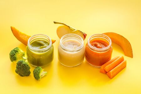Vegetable and fruits puree for feed babies on yellow background.