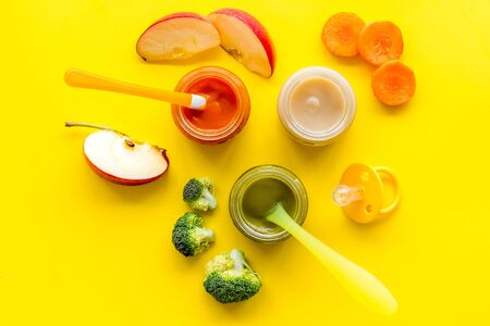Baby food. Colorful puree in glass jars near vegetables and fruits on yellow background top view.