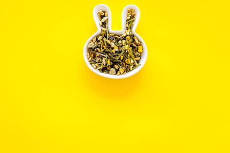Pet food for rabbits in rabbit-shaped bowl on yellow background top view.