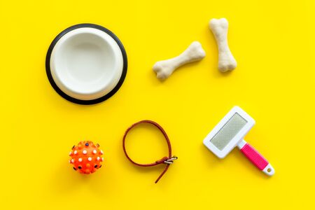 Set of treats and toys for pets with bones, collar and bowl on yellow background top view. Фото со стока - 133401599