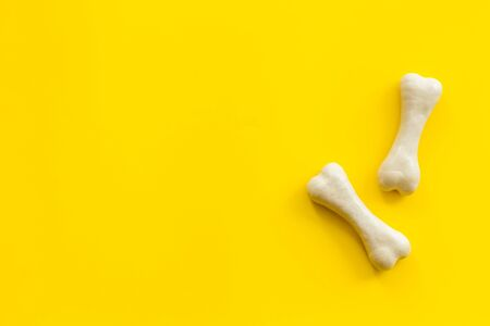 Treats for dogs. Chewing bones on yellow background top view. 写真素材