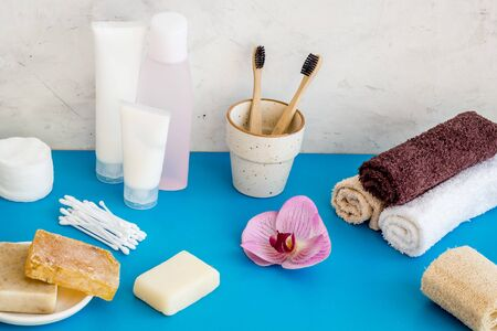 Bathroom accessories set with tooth brushes and towels on blue background.