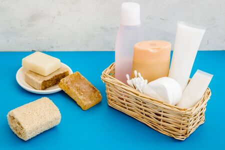 Bathroom cosmetics and hygiene products on blue background.