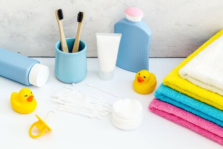 Baby bathroom cosmetics near pacifier and rubber duck on white background.