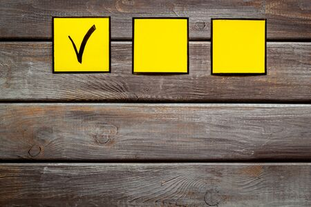 Check mark in yellow check-box on dark wooden background top view. Reklamní fotografie