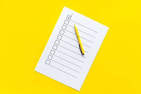 Empty check list ready to fill on yellow background top view. Reklamní fotografie