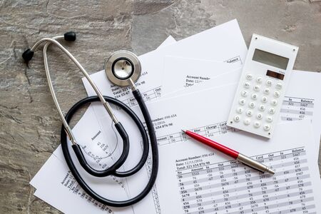Health insurance concept. Stethoscope near financial documents and calculator on grey background top view. Stock fotó - 133417866