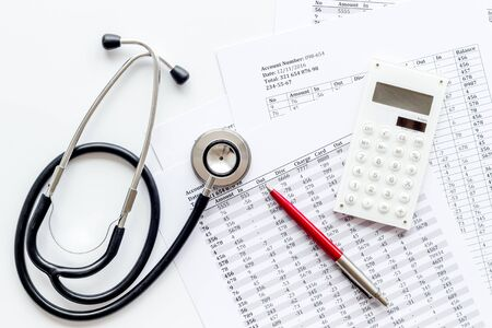 Health insurance concept. Stethoscope near financial documents and calculator on white background top view.