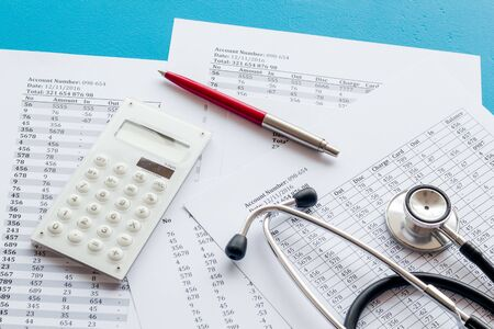 Health insurance concept. Stethoscope near financial documents and calculator on blue background. Stock fotó - 133417937