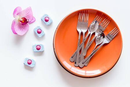 Dry detergent for dishwashing near plates and orchid flower on white background top view