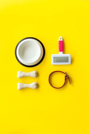 Pets accessories like bones, collar and bowl on yellow background top view flat lay