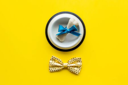 Dogs birthday concept. Chewing bones with bow and bow-tie on yellow background top view.