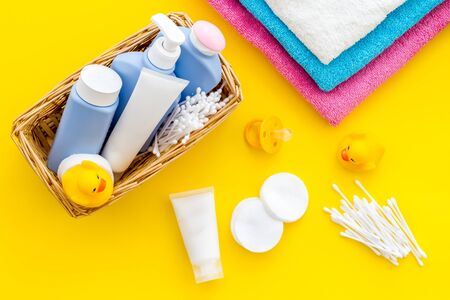 Baby bathroom cosmetics near pacifier and rubber duck on yellow background. Stock Photo
