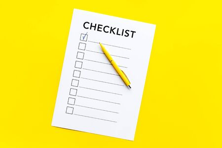 Checklist close up and pen on yellow background top view.