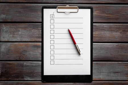 Empty check list ready to fill on dark wooden background top view. Reklamní fotografie
