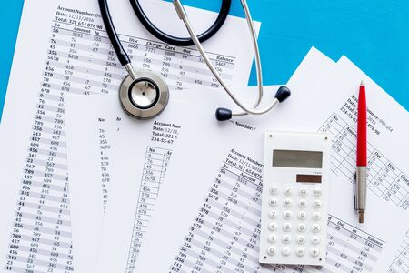 Health insurance concept. Stethoscope near financial documents and calculator on blue background top view Stock fotó