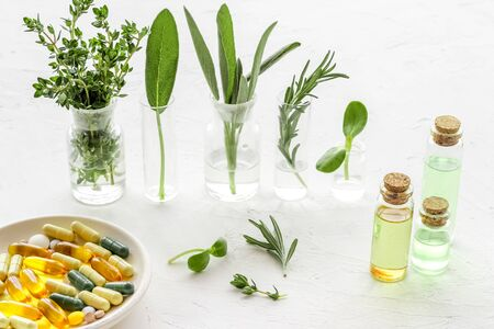 Healing herbs in glasses and medicine on white background