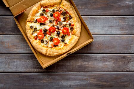 Order pizza to home or office. Italian food in box on dark wooden background top view copy space 스톡 콘텐츠