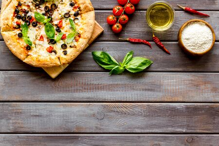 Traditional italian food: pizza on dark wooden background top view copy space