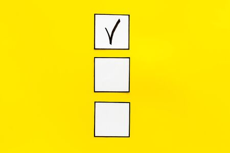 Check mark in check-box on yellow background top view copy space