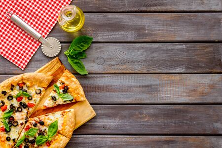 Pizza with tomato, basil, olives, cheese on dark wooden background top view.