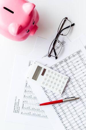 Concept de paiement des taxes. Documents financiers, tirelire, calculatrice sur la vue de dessus de fond blanc.